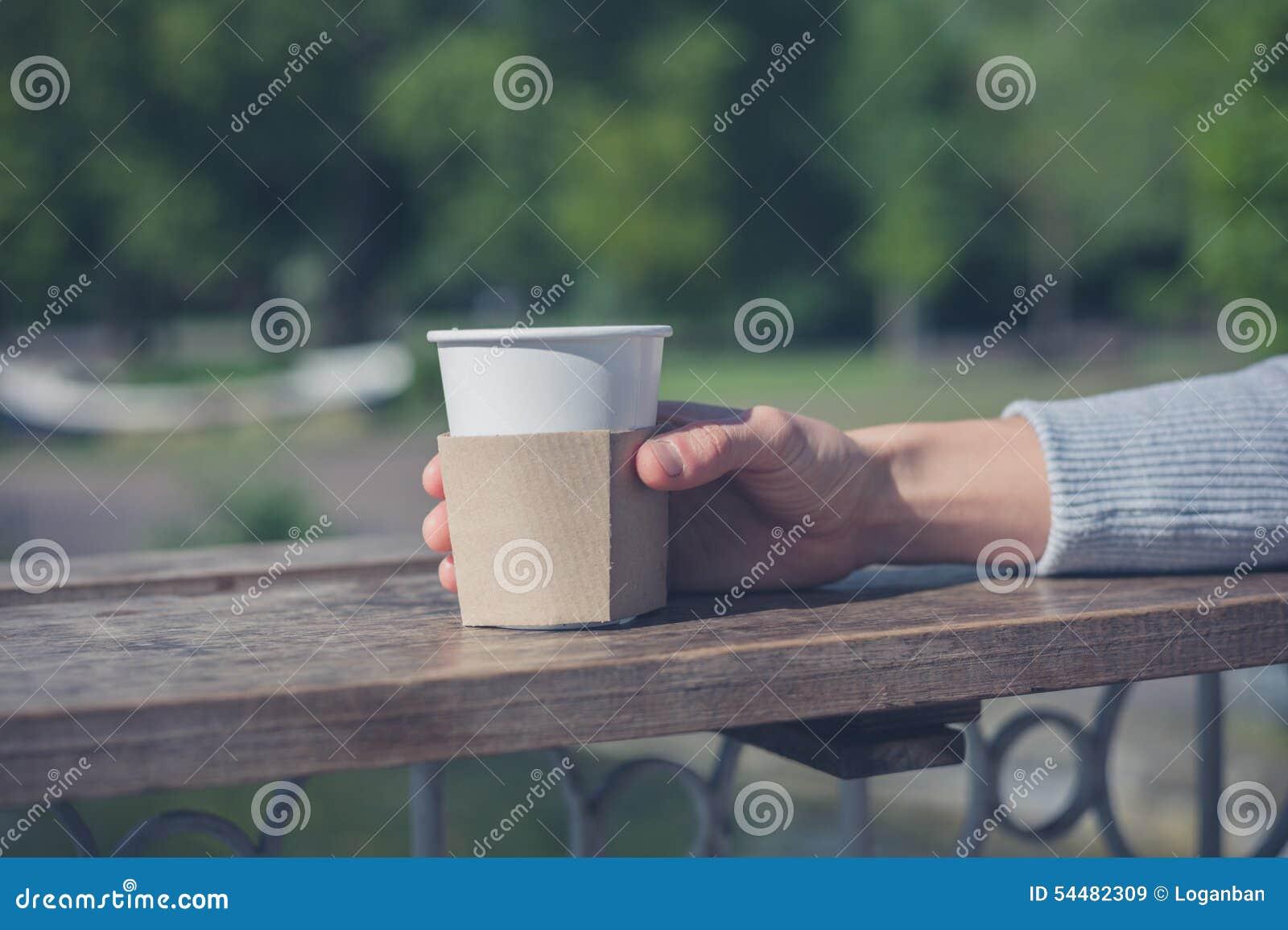 Женская рука держа бумажный стаканчик