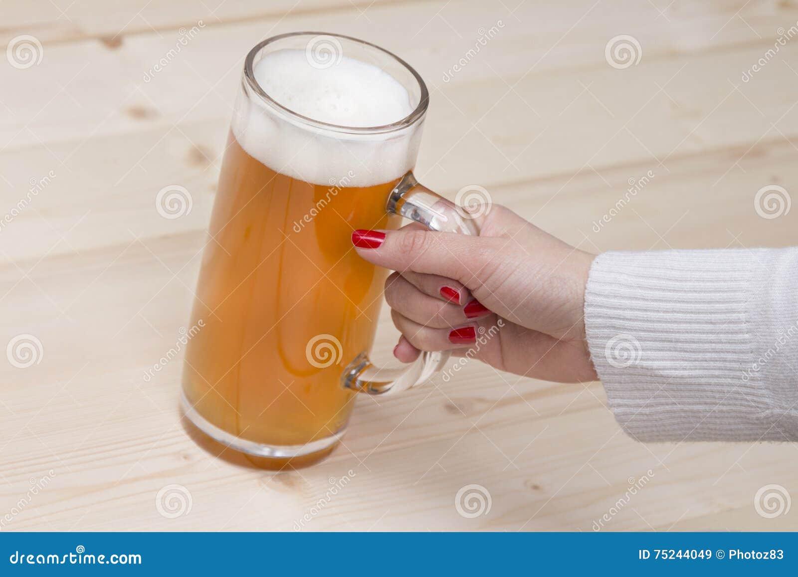Женская рука держа кружку пива проекта
