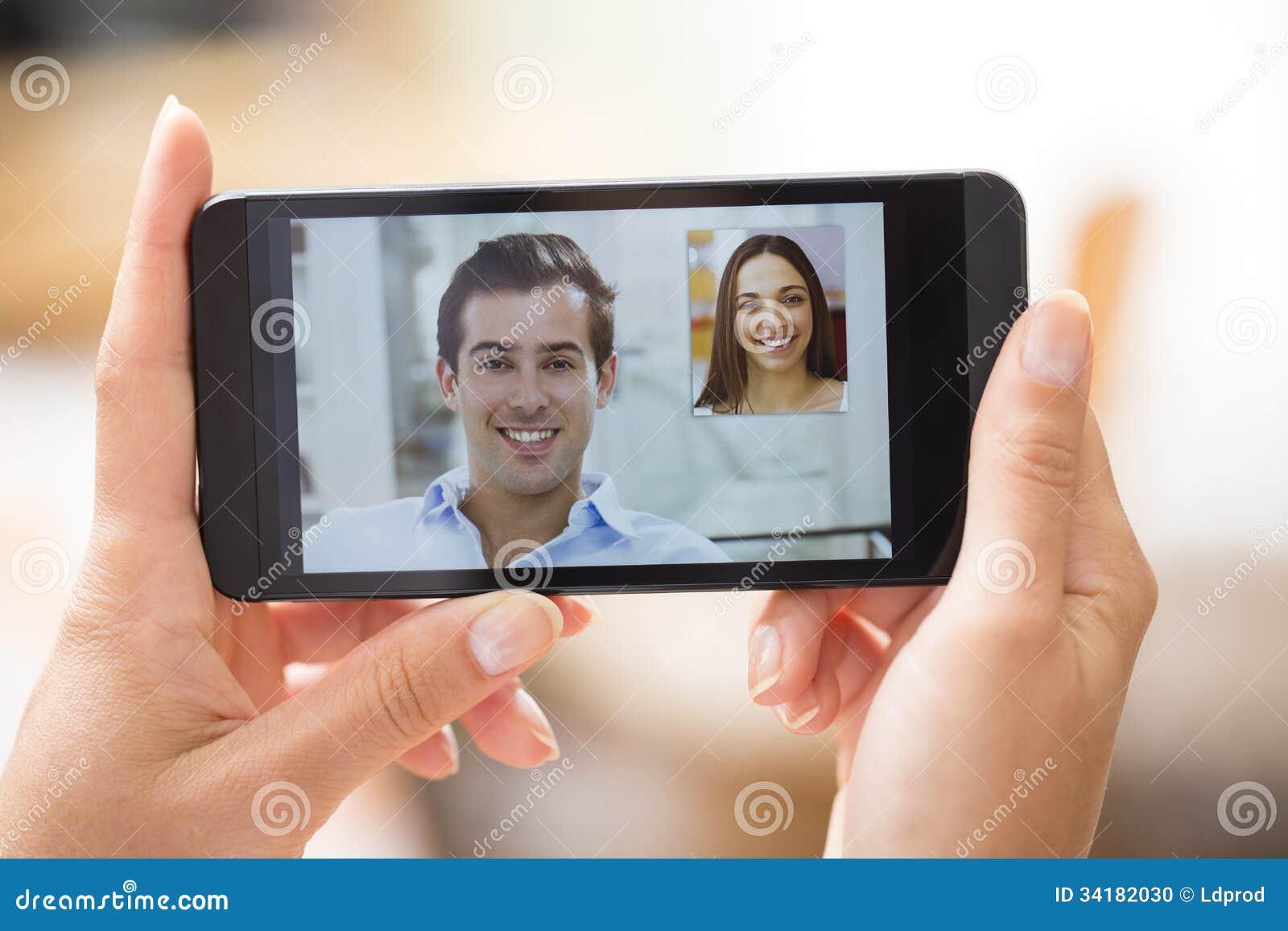 Женская рука держа smartphone во время видео skype