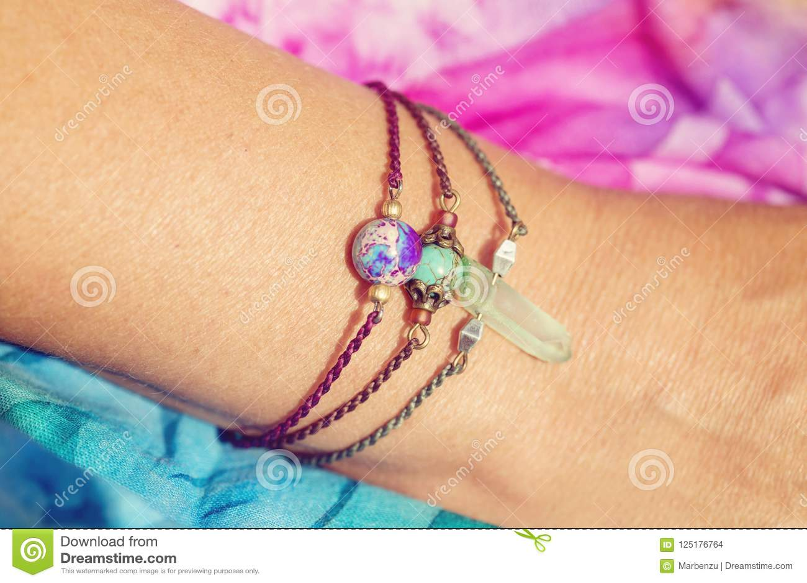 Женская рука нося естественные каменные браслеты шарика