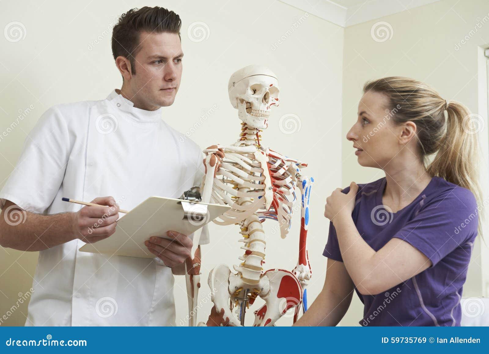 Женская терпеливая описывая травма плеча к Osteopath