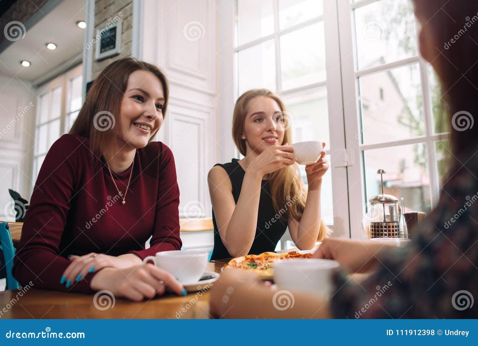 Женские друзья выпивая кофе имея приятный переговор в уютном романтичном ресторане