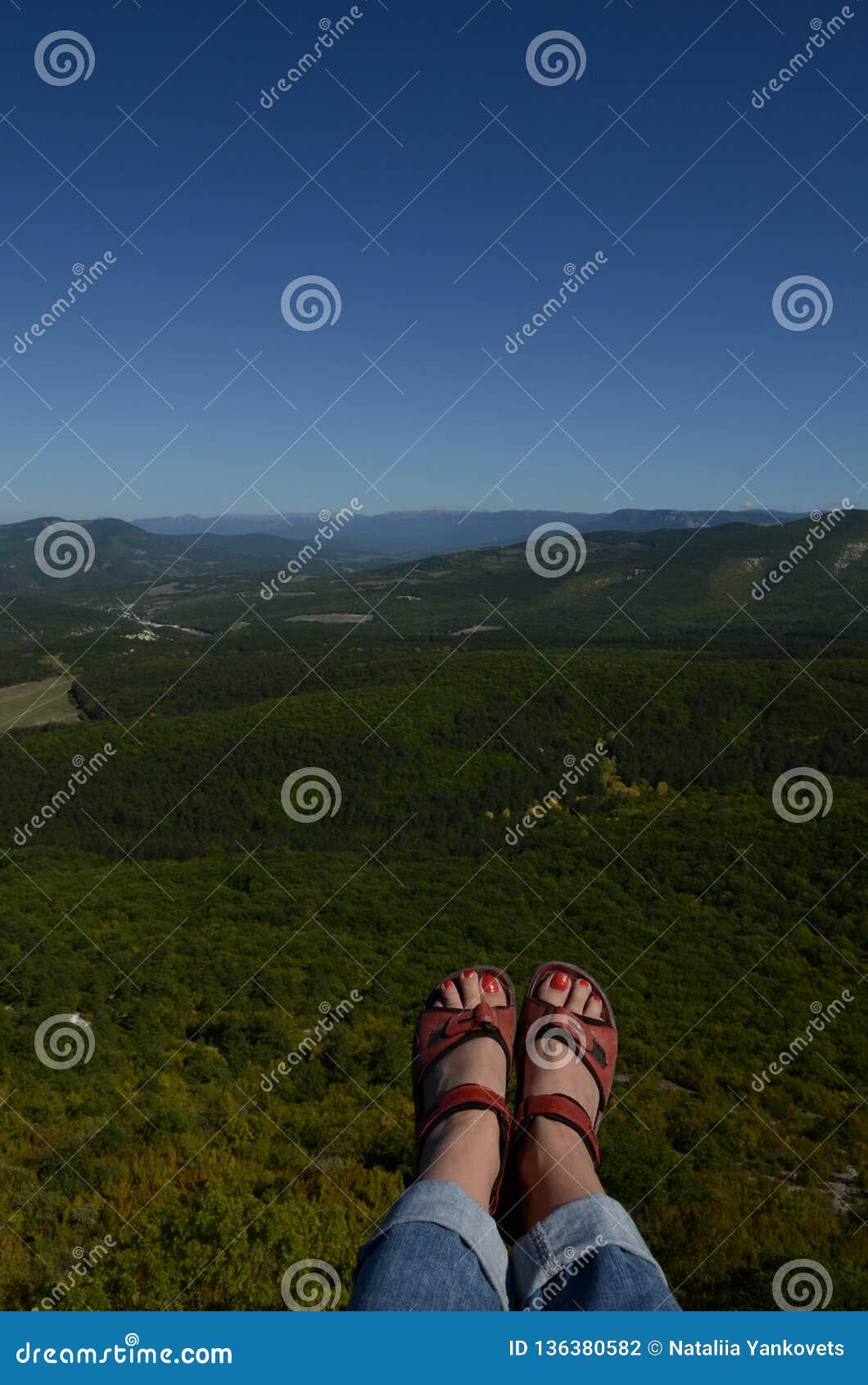 Женские ноги в trekking ботинках над огромной пропастью против предпосылки зеленого леса и голубого неба Крым