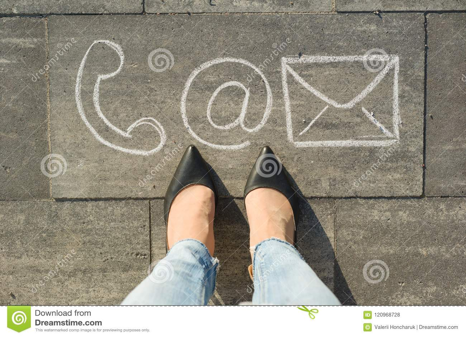 Женские ноги с символами контакта знонят по телефону почте и письму, написанным на сером тротуаре, сообщение или свяжутся мы конц