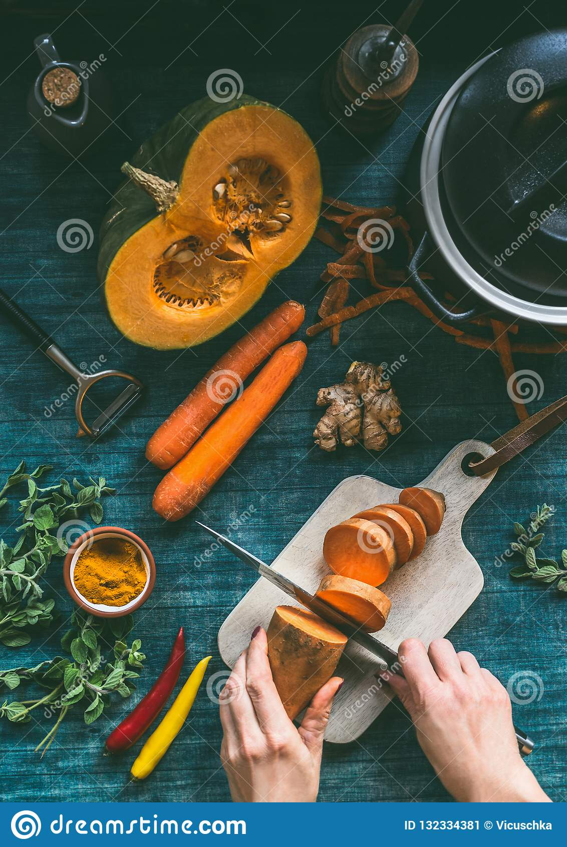 Женские руки варя здоровые суп или овощи тушат с ингредиентами оранжевого цвета вегетарианскими: тыква, моркови, сладкие картофел
