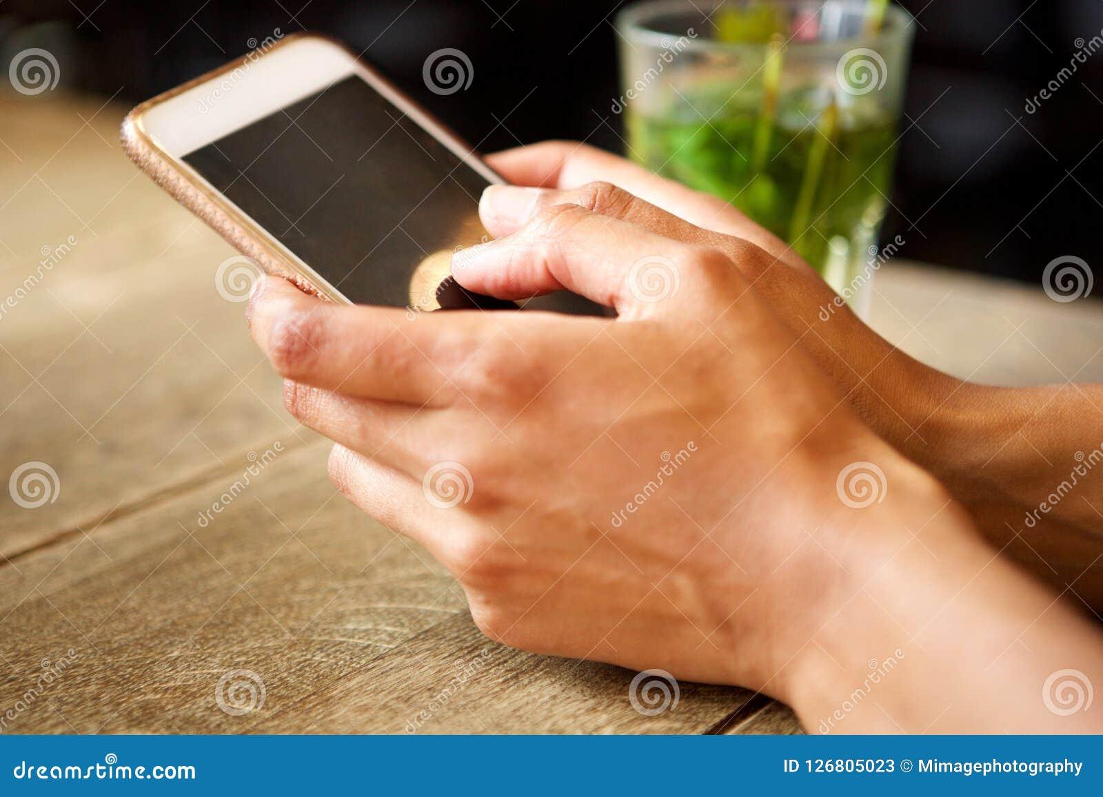 Женские руки держа мобильный телефон на таблице с напитком