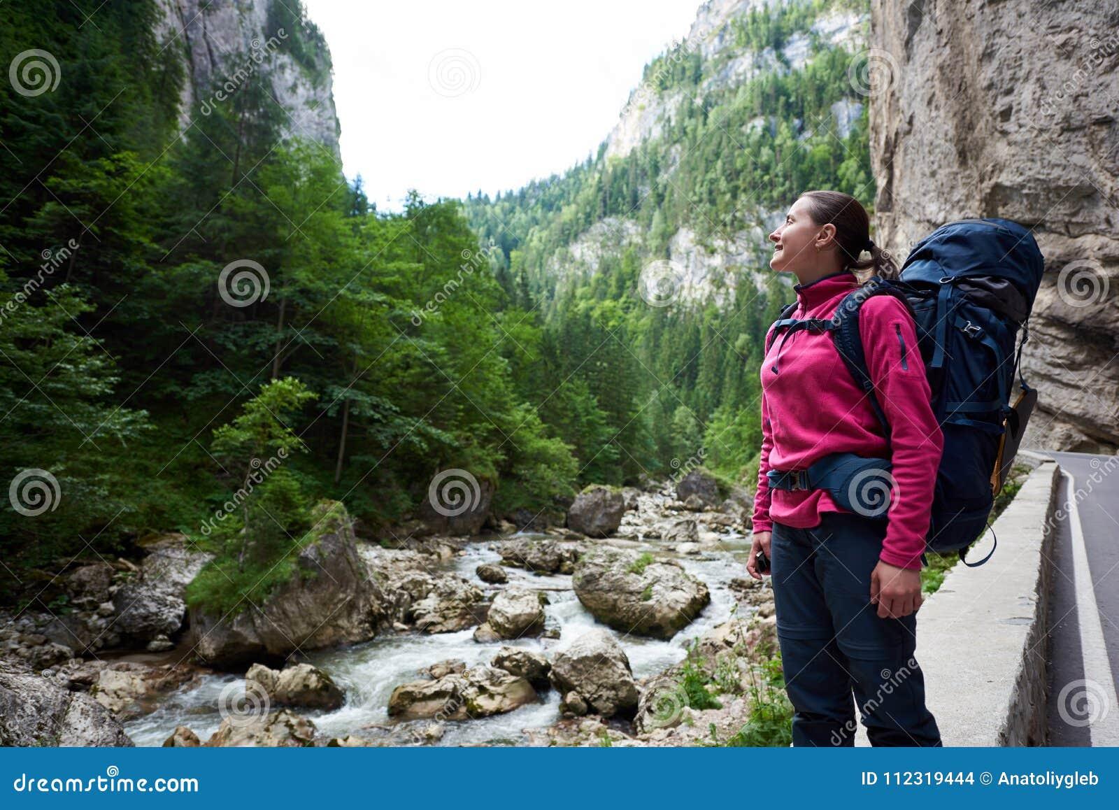 Женский альпинист восхищая изумительный взгляд зеленых травянистых скалистых гор и потока воды в горной области в Румынии