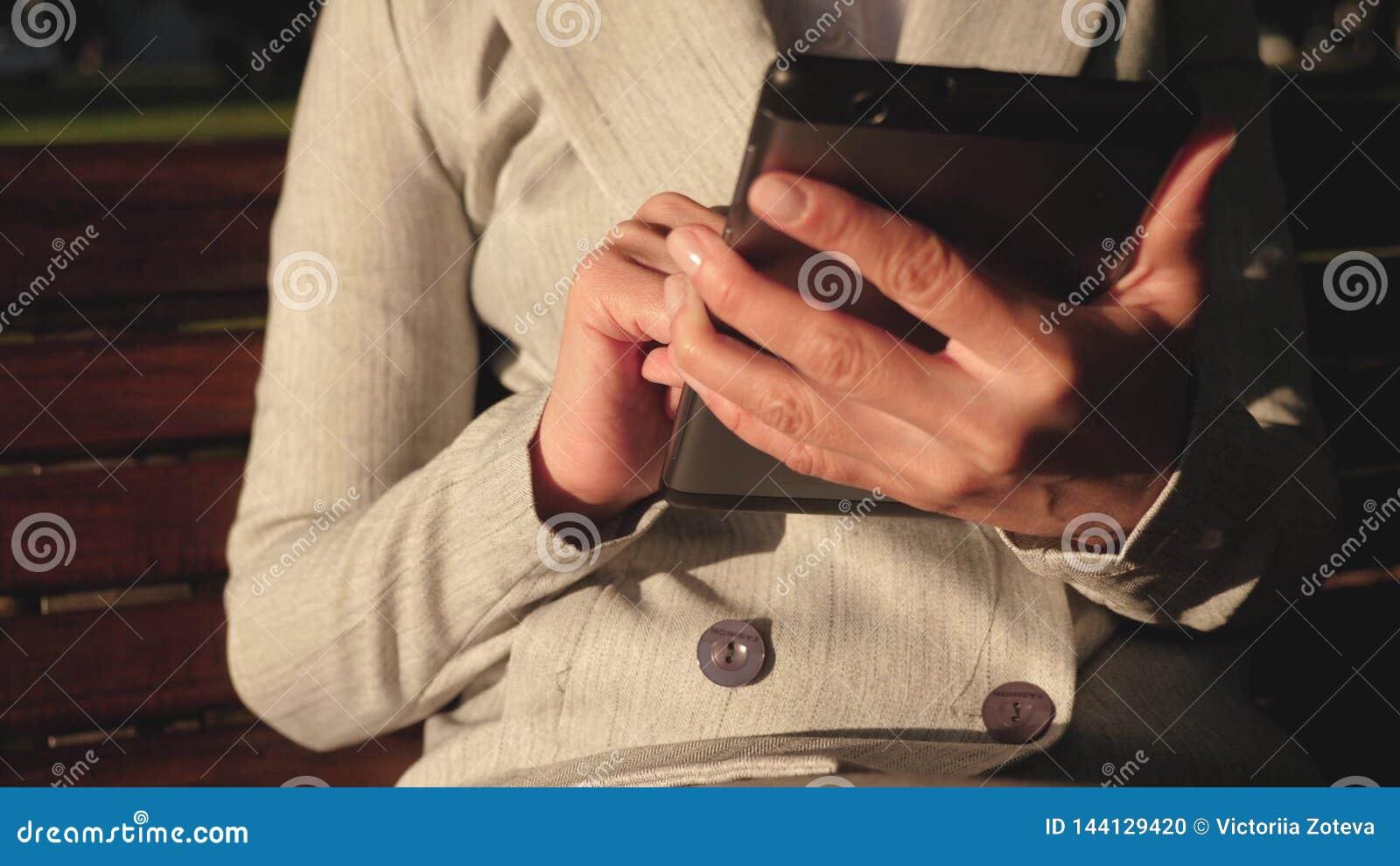 Женский бизнесмен носит стекла и работает с планшетом и проверяет электронную почту в парке лета на стенде