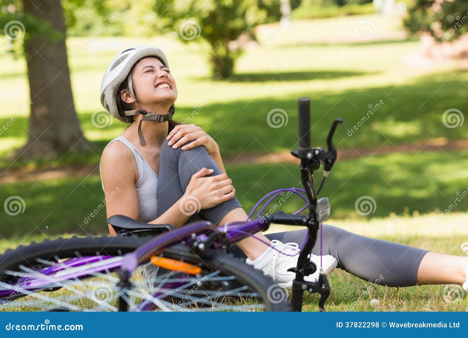 Женский велосипедист при нога повреждения сидя в парке