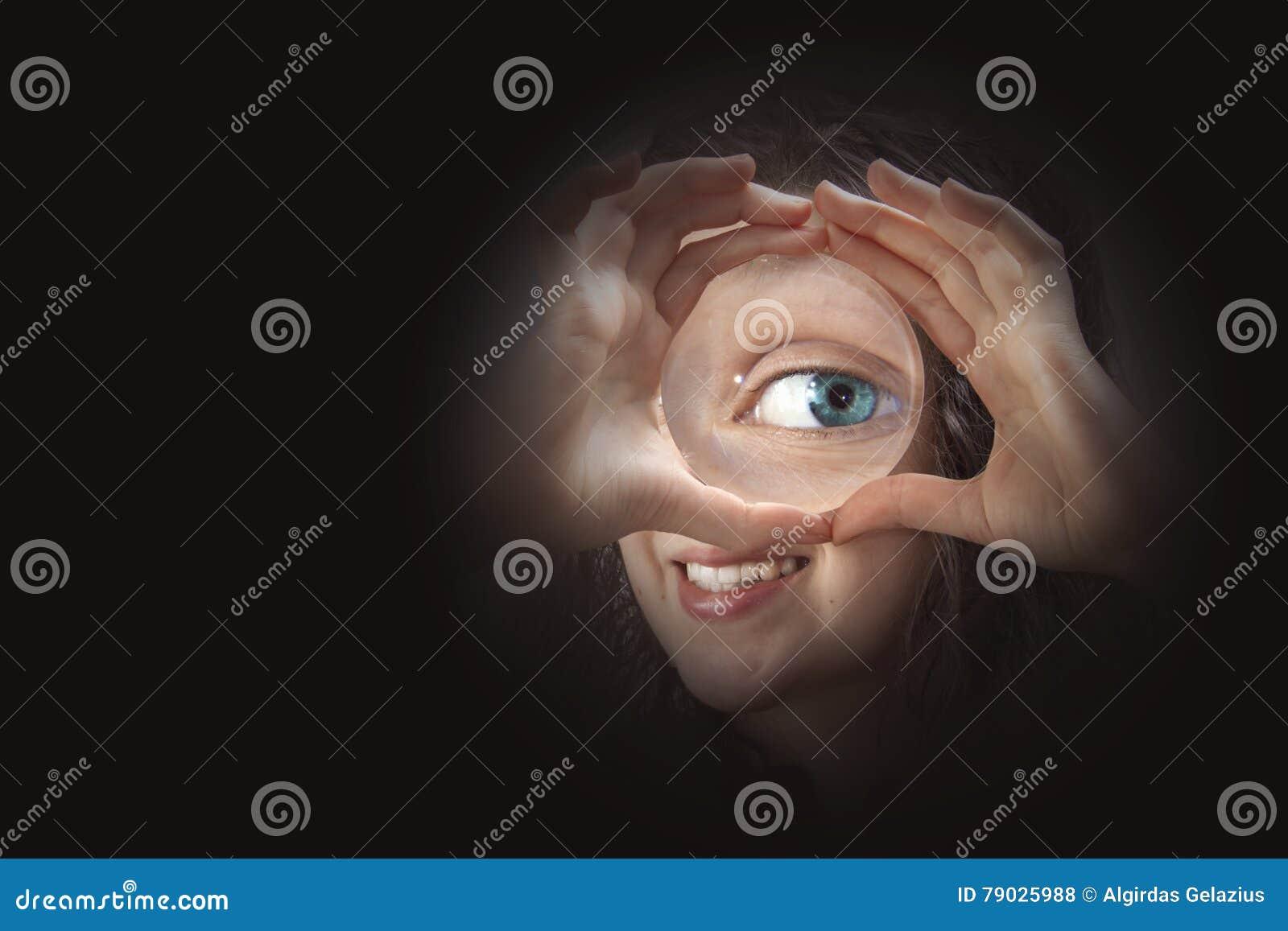 Женский глаз смотря через конец лупы вверх
