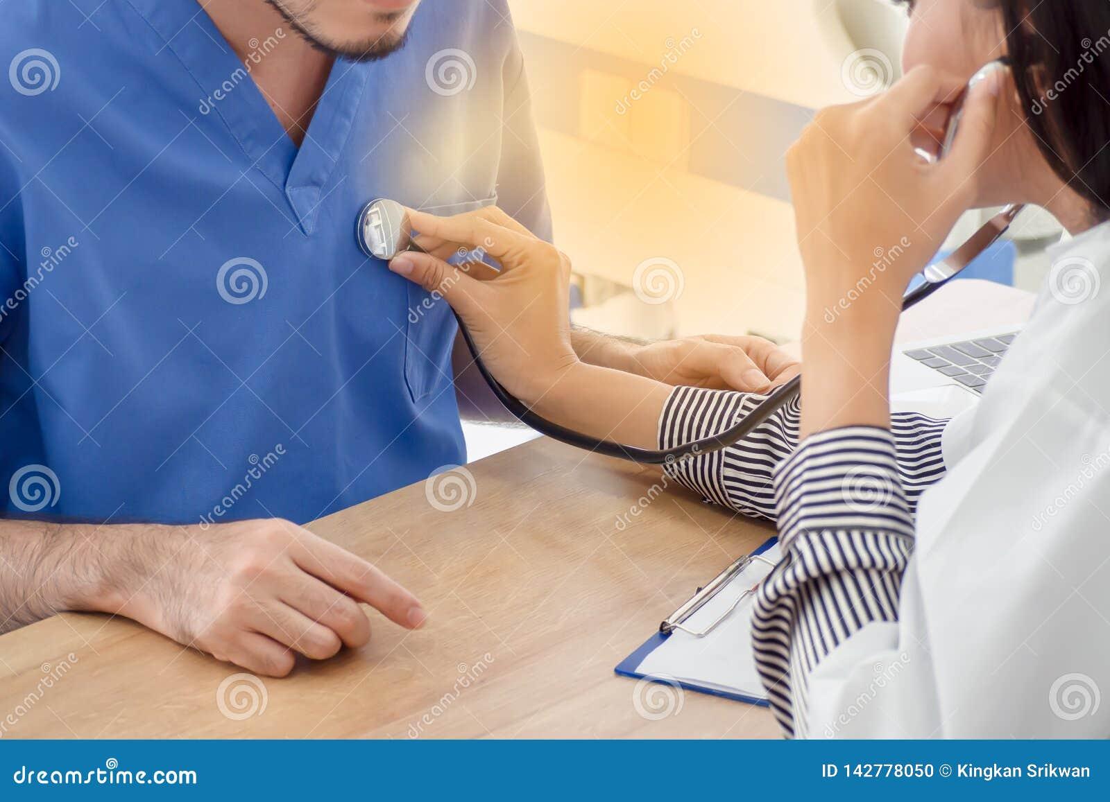 Женский доктор использует стетоскоп на мужском пациенте