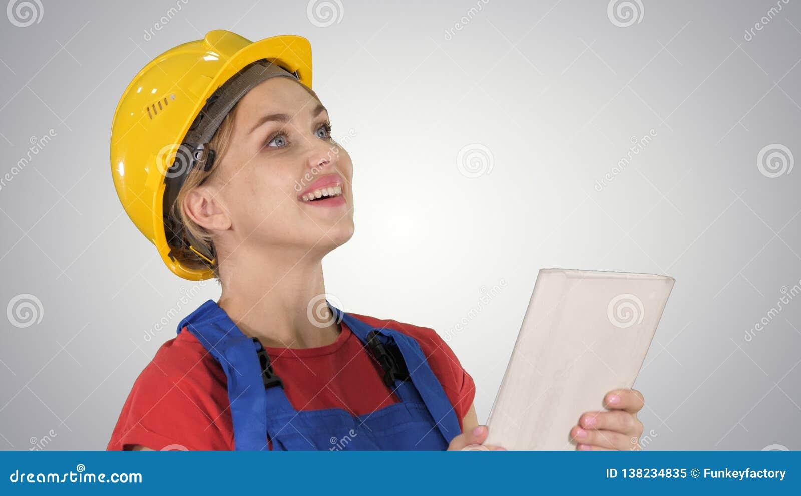 Женский инженер по строительству и монтажу с планшетом на строительной площадке на предпосылке градиента