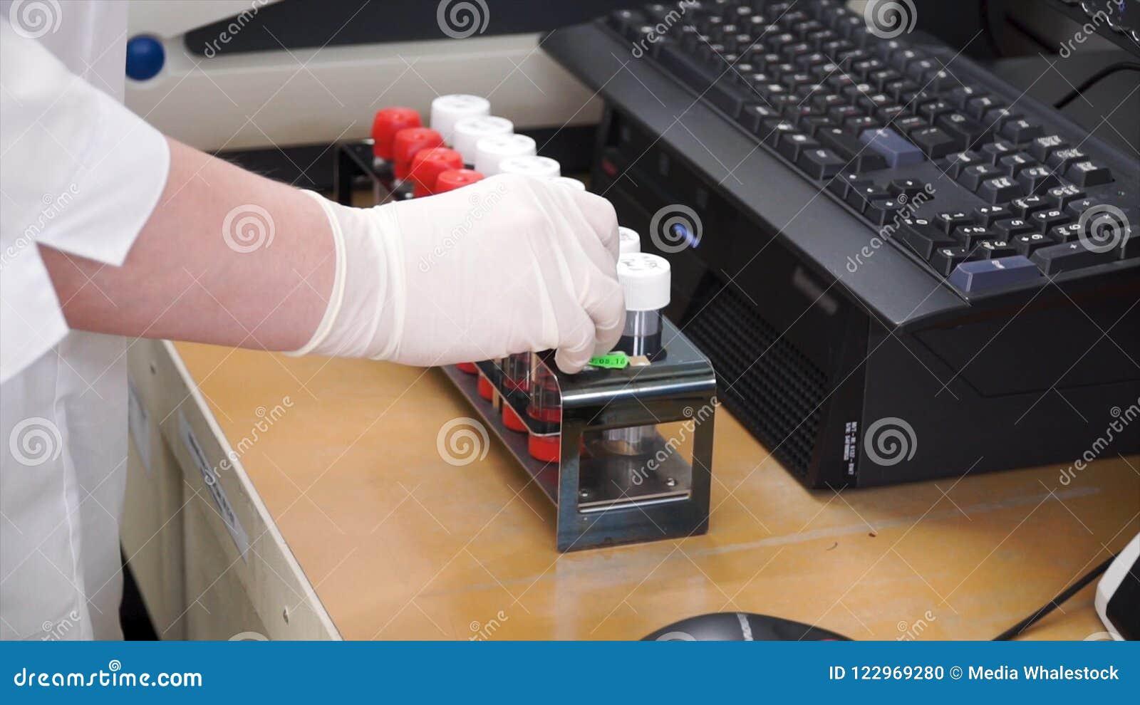 Женский медицинский или научный исследователь используя пробирки на лаборатории зажим Женский ученый анализирует жидкость в