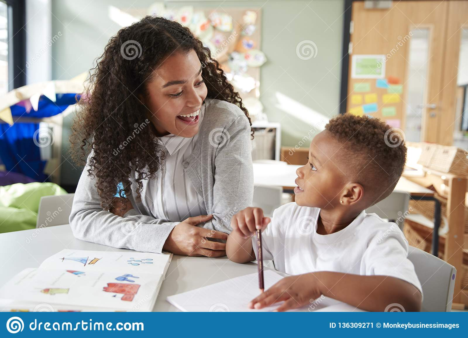 Женский младенческий школьный учитель работая одно на одном с молодым школьником, сидя на таблице усмехаясь на одине другого, кон