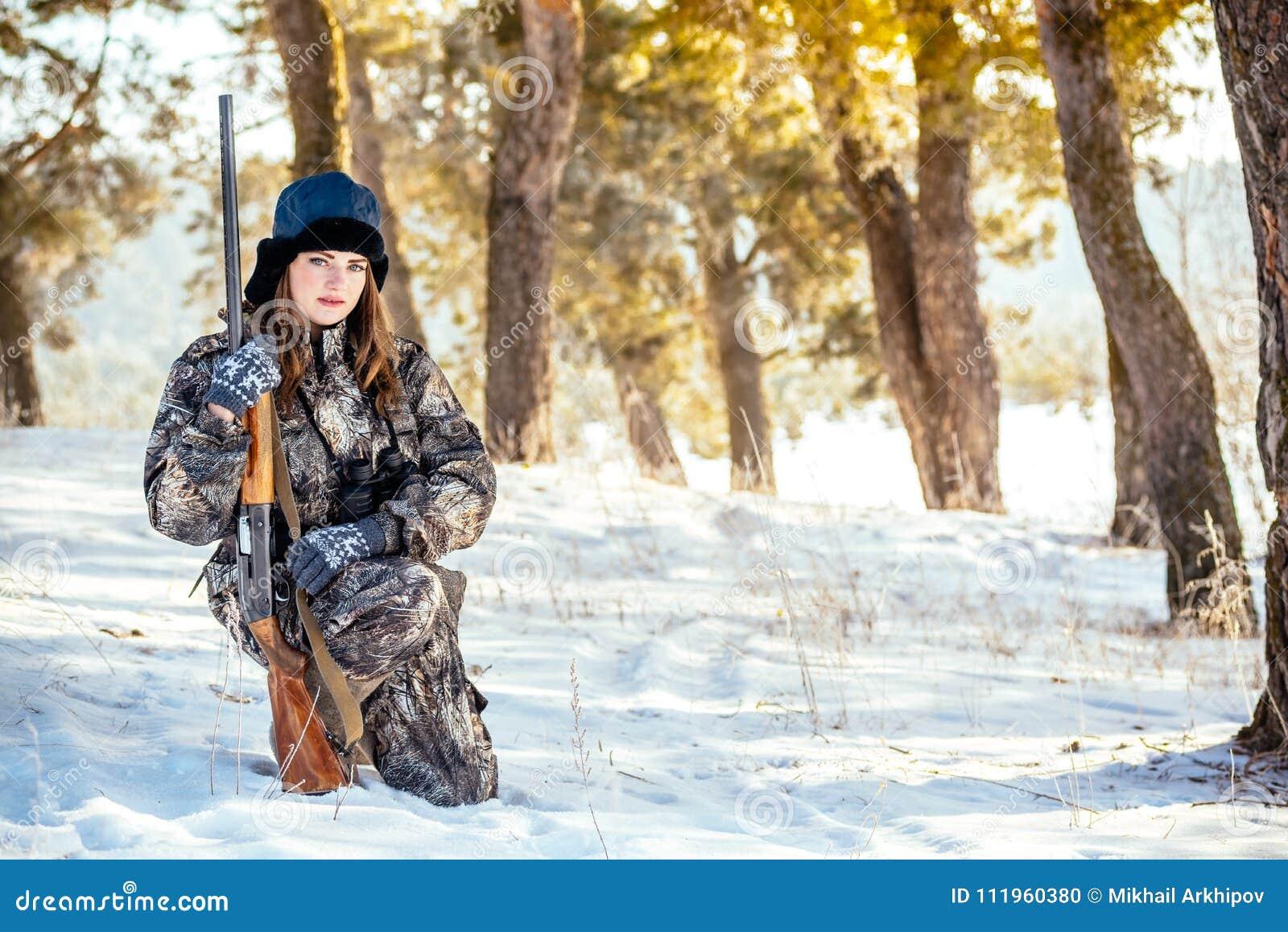 Женский охотник в камуфлировании одевает готовое для того чтобы поохотиться, держащ оружие a