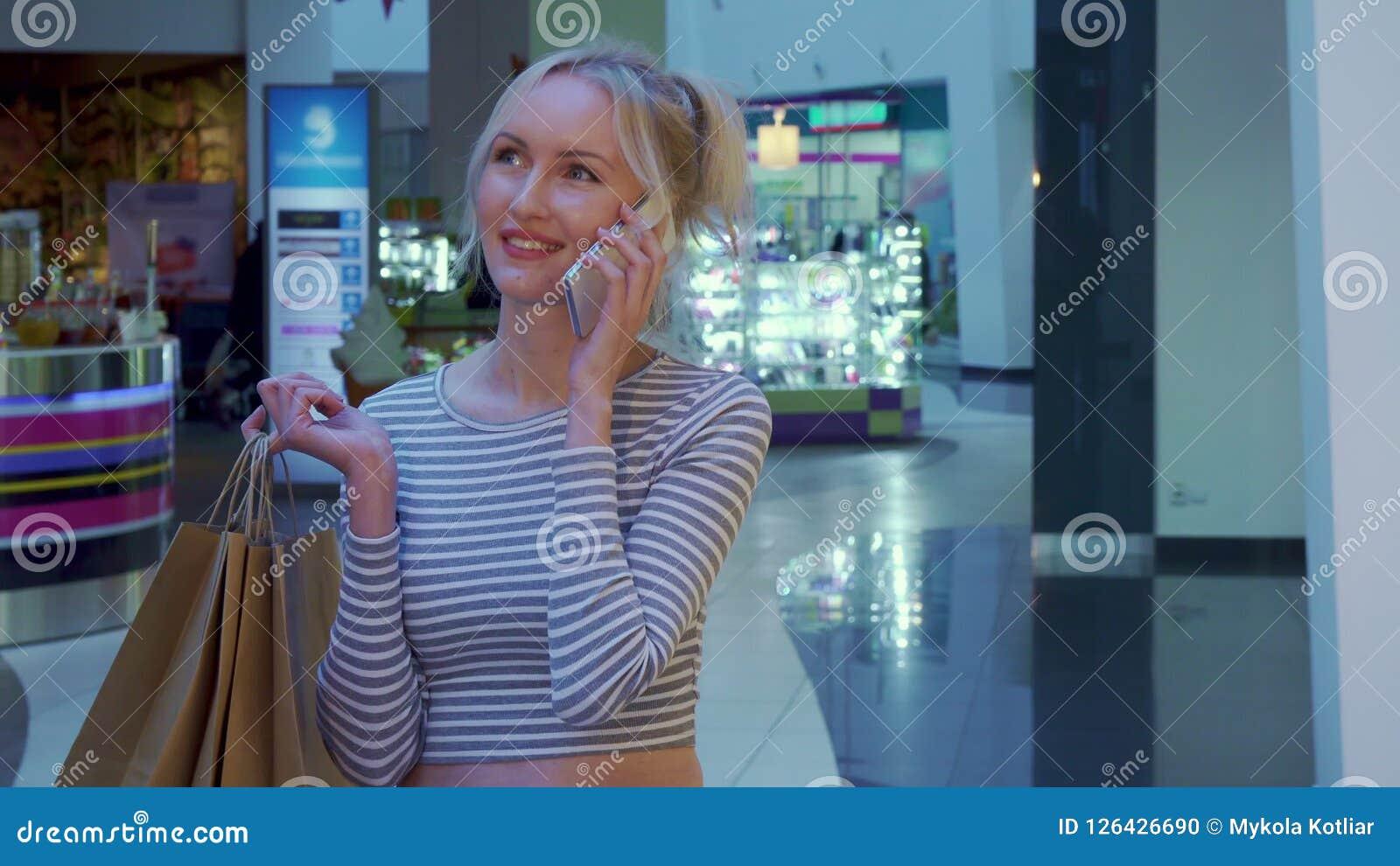 Женский покупатель говорит на телефоне на моле