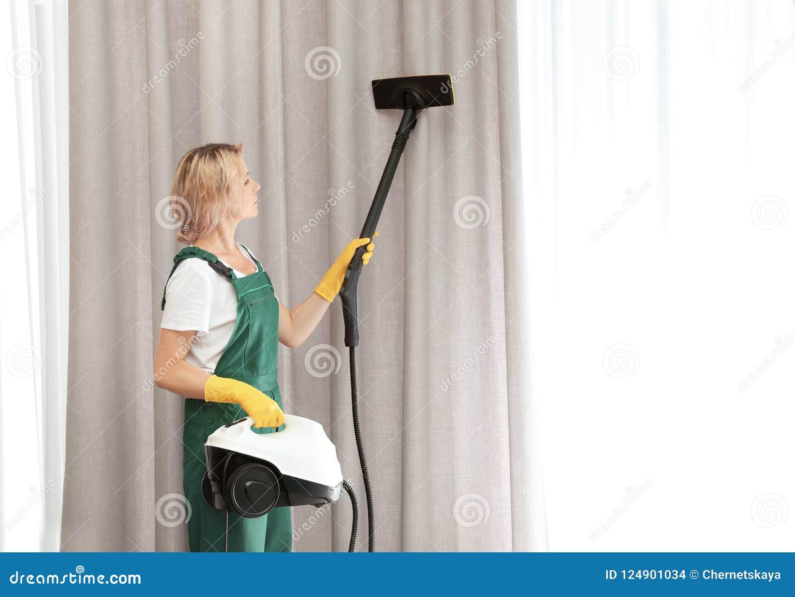 Женский привратник извлекая пыль от острословия занавеса