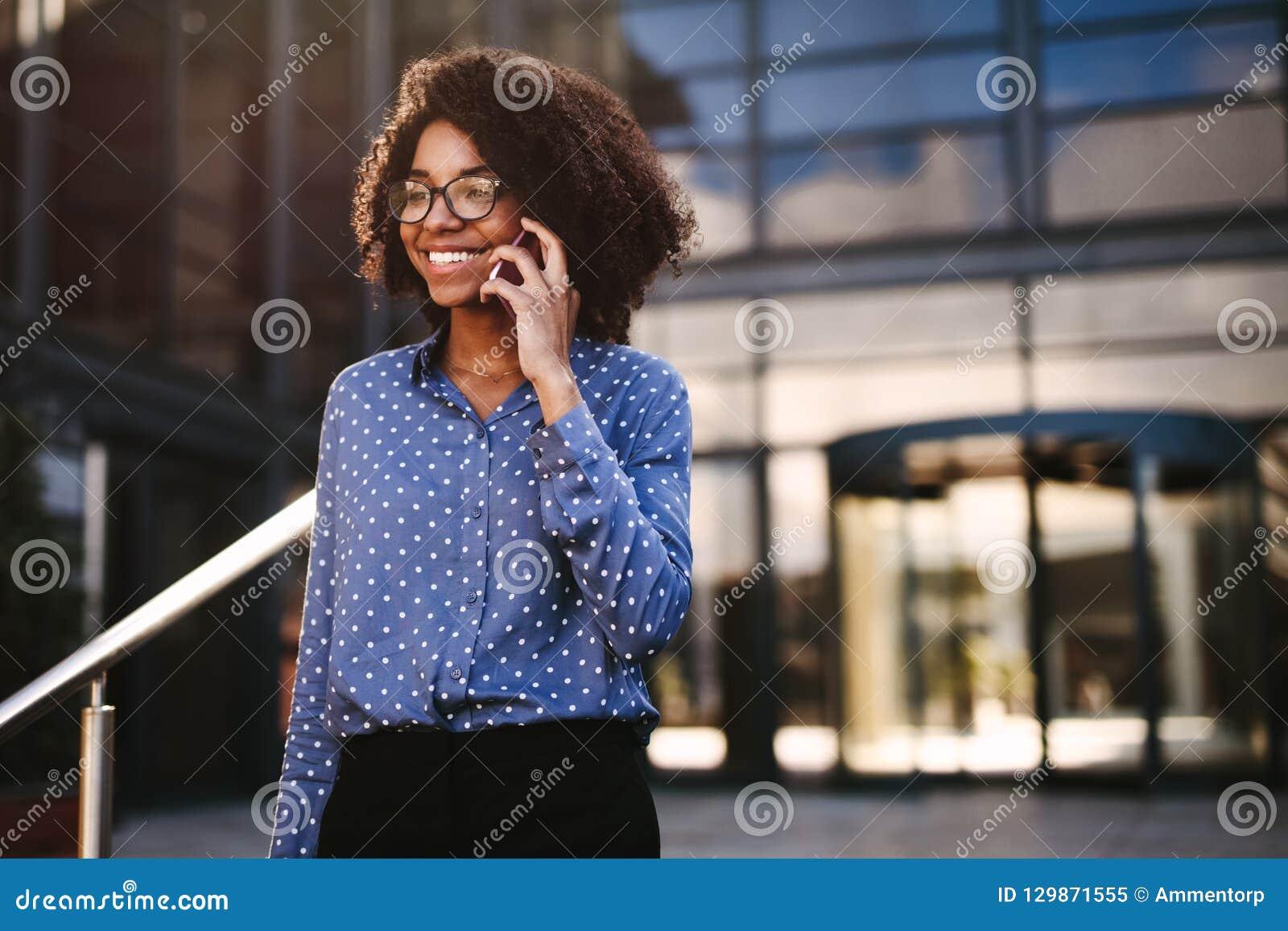 Женский профессионал дела идя снаружи используя телефон