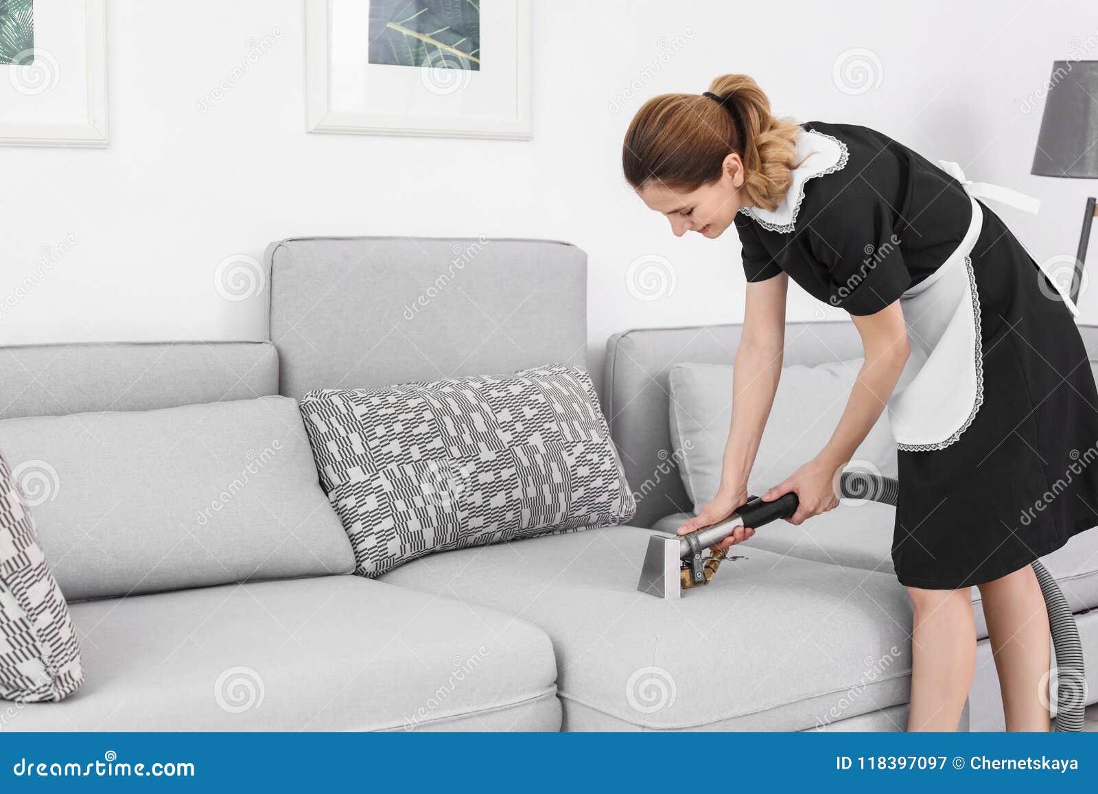 Женский работник извлекая грязь от софы с профессиональным пылесосом, внутри помещения