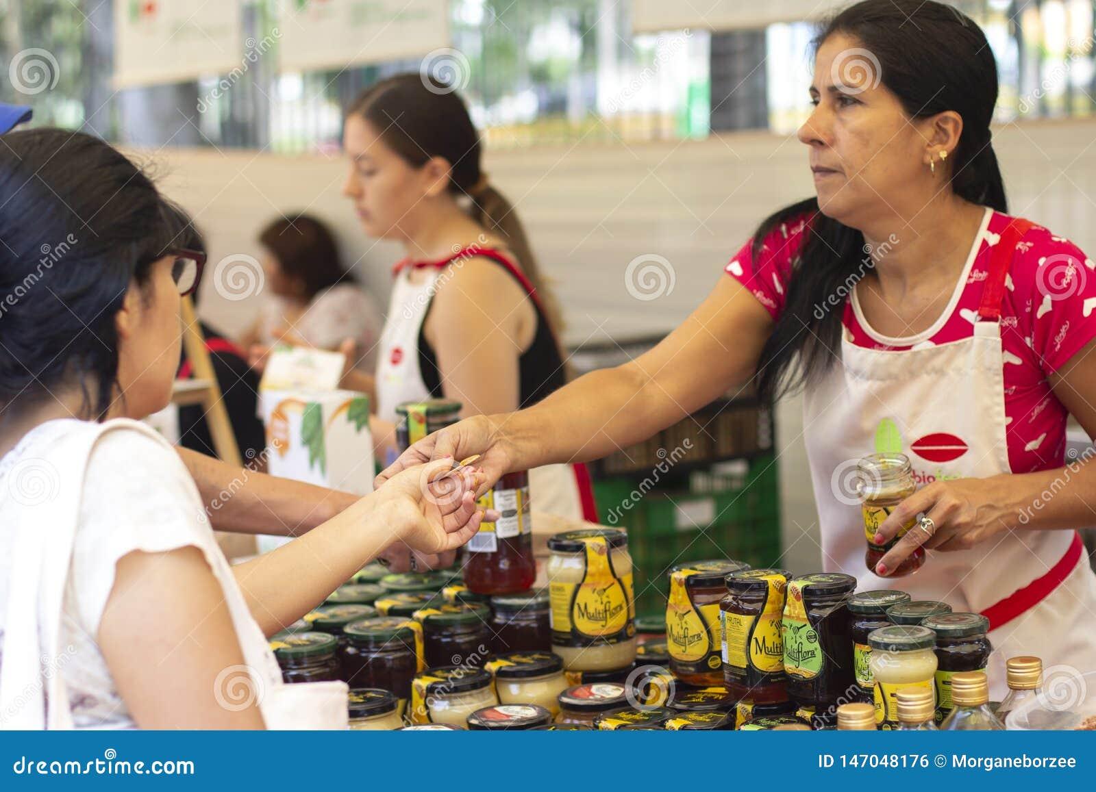 """Женский работник на уличном рынке давая образец меда на """"bioferia """""""
