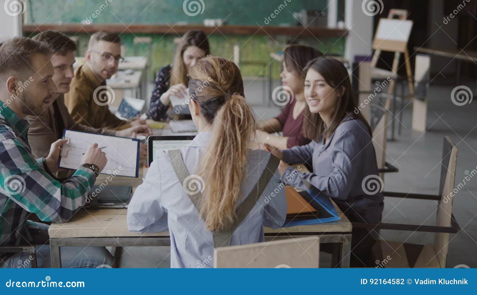 Женский руководитель группы приносит документы к творческой команде дела Смешанная группа лицо одной расы людей встречая в соврем