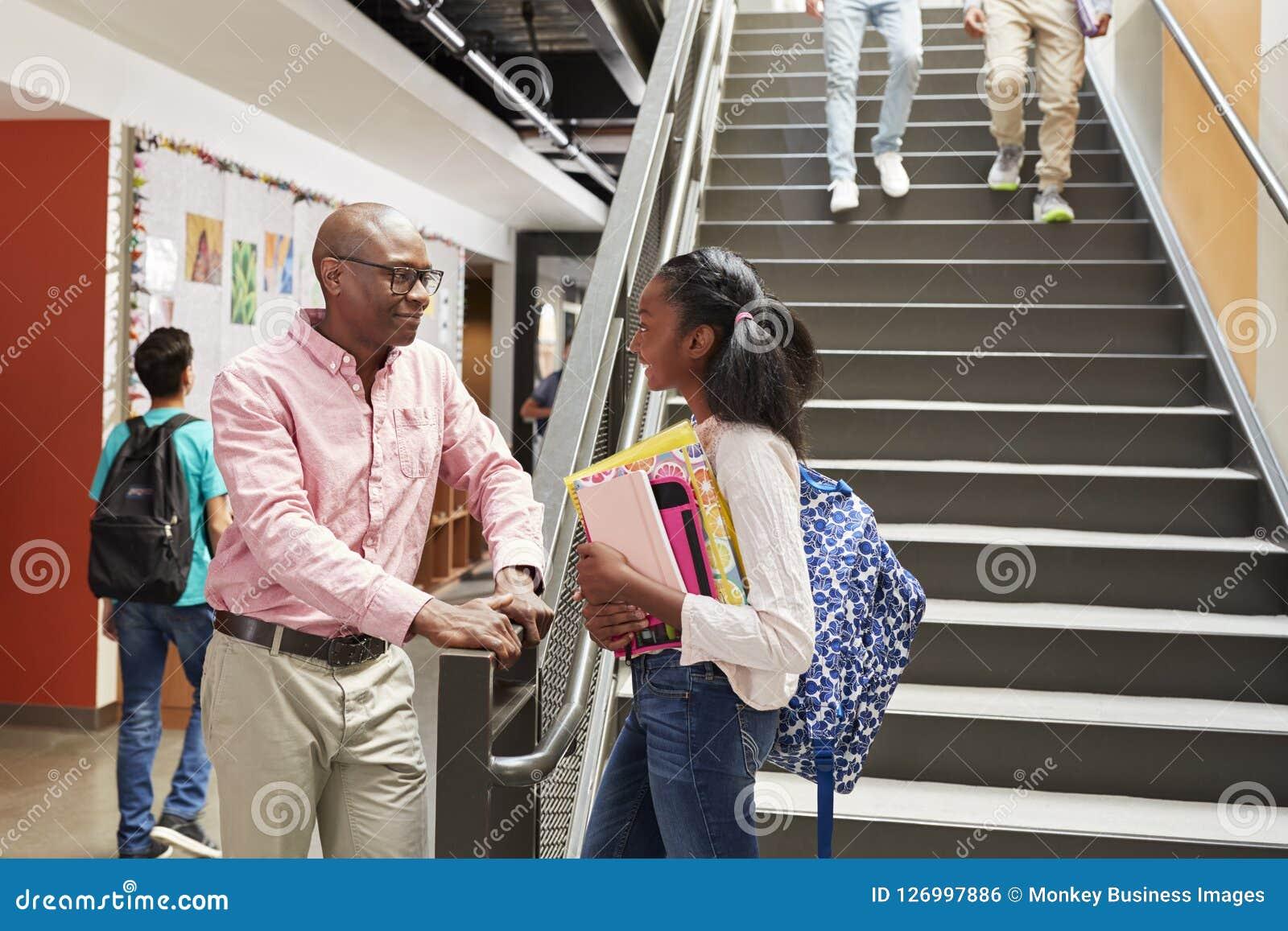 Женский студент средней школы разговаривая с учителем в занятом коридоре