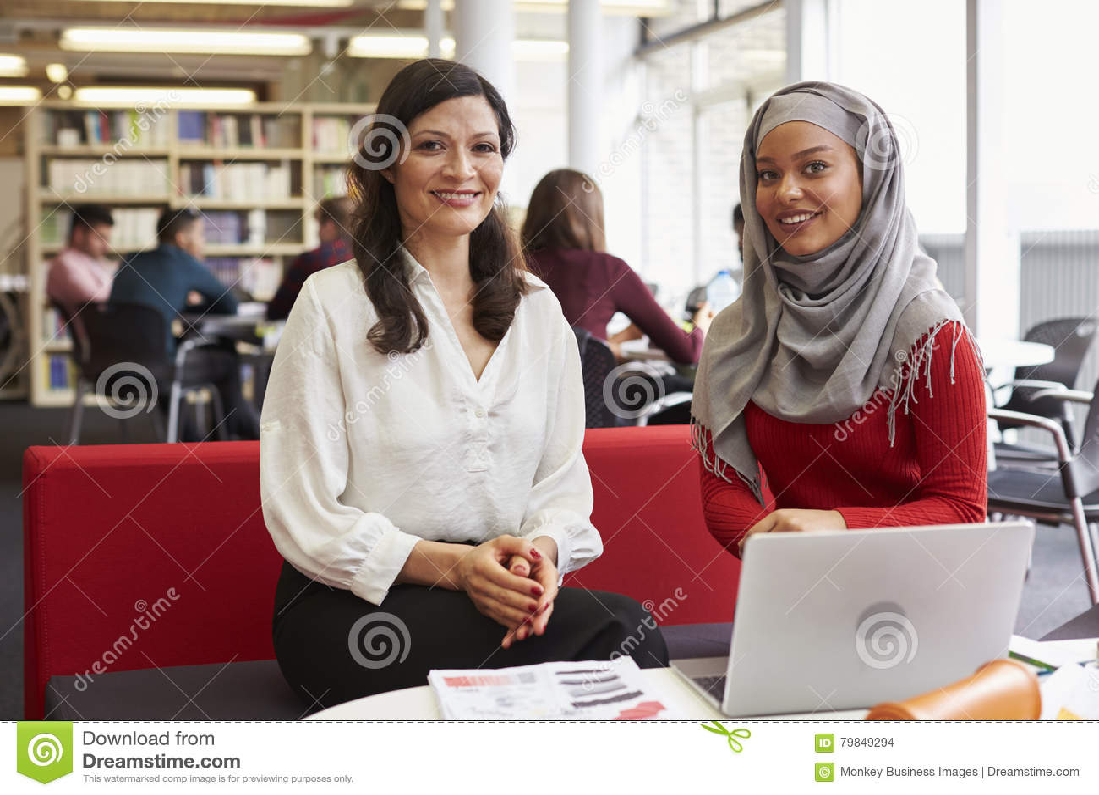 Женский студент университета работая в библиотеке с гувернером