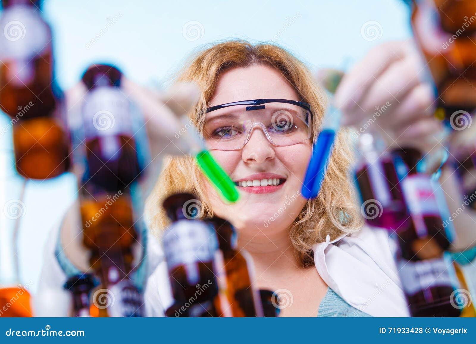 Женский студент химии с склянкой испытания стеклоизделия