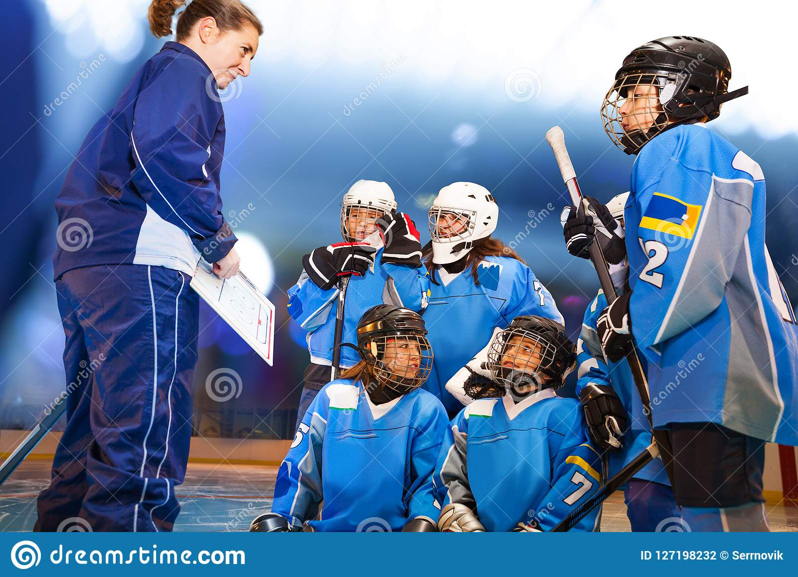 Женский тренер показывая стратегию игры к команде хоккея на льде