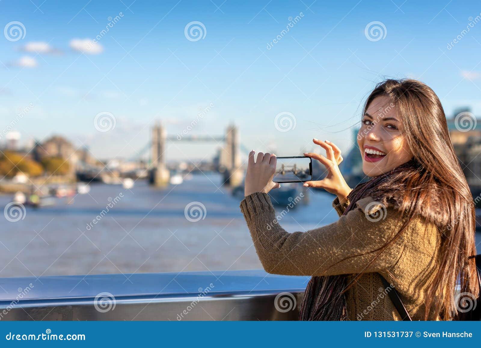Женский турист Лондона фотографирует мост башни