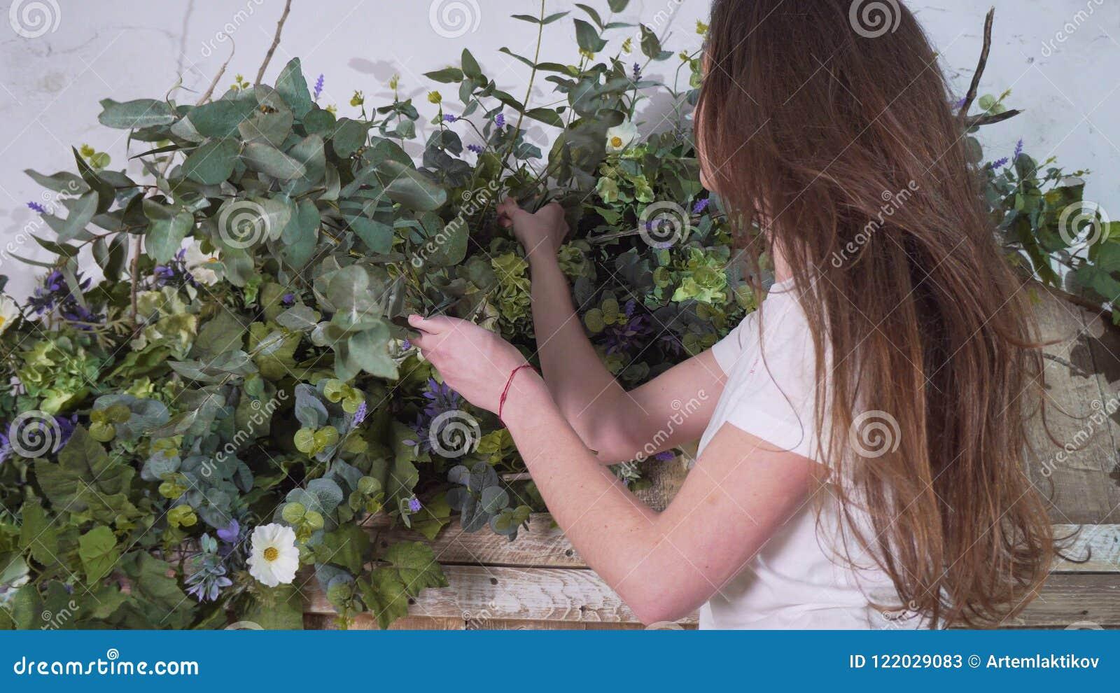 Женский флорист стоит на высоте с ветвями евкалипта в ее руках и украшает цветки на красивых деревянных стробах