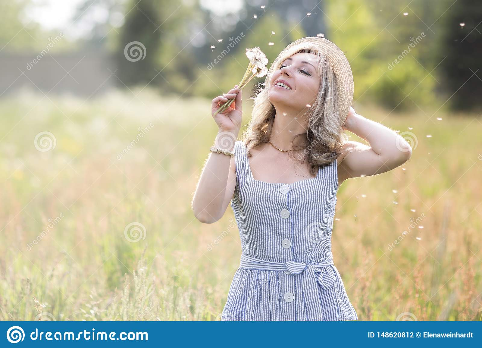 Женский outdoors портрета женщина в соломенной шляпе в поле цветка с букетом полевых цветков