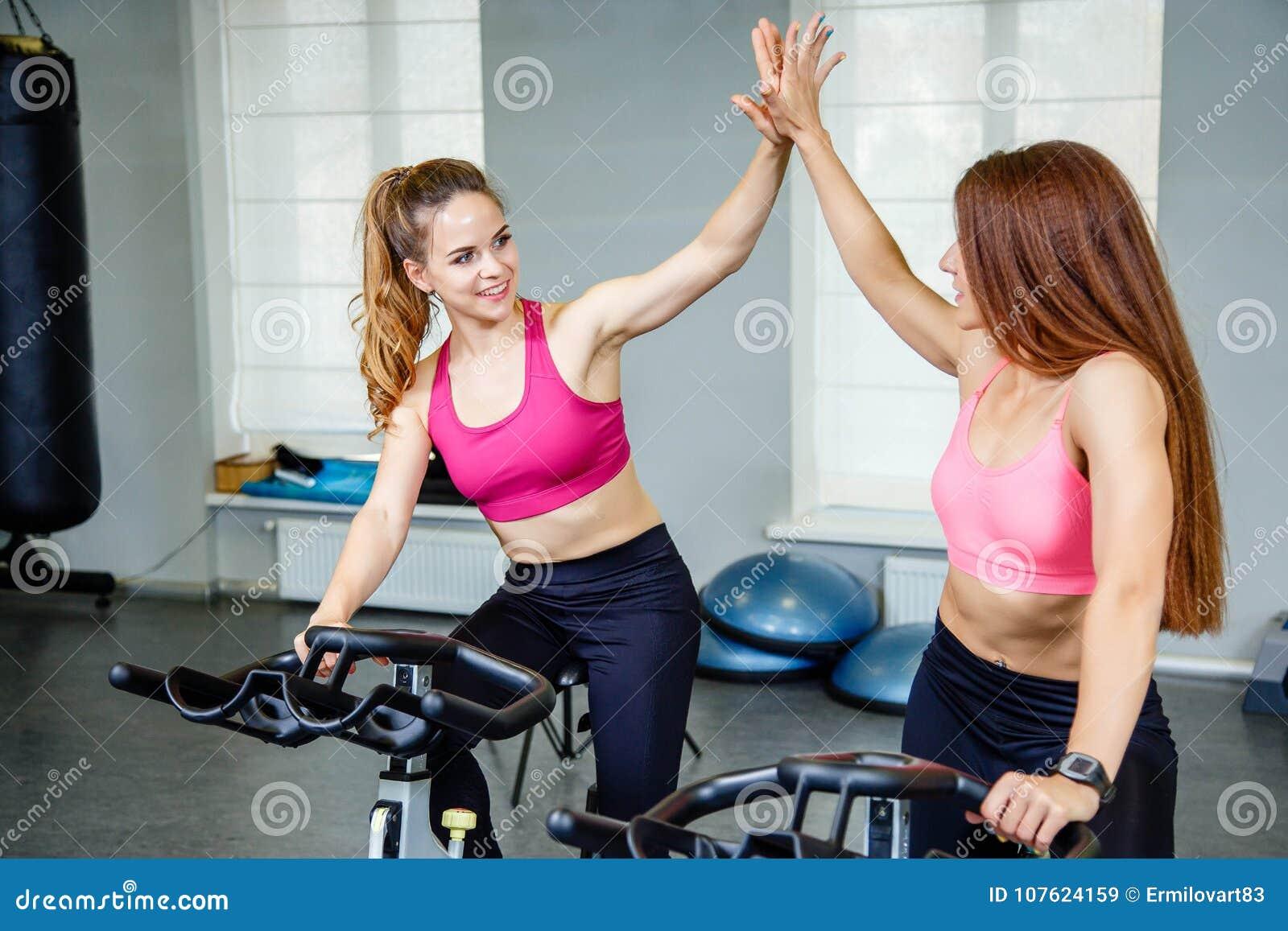 2 женских друз нося sportswear давая максимум 5 пока cardio разминка в спортзале