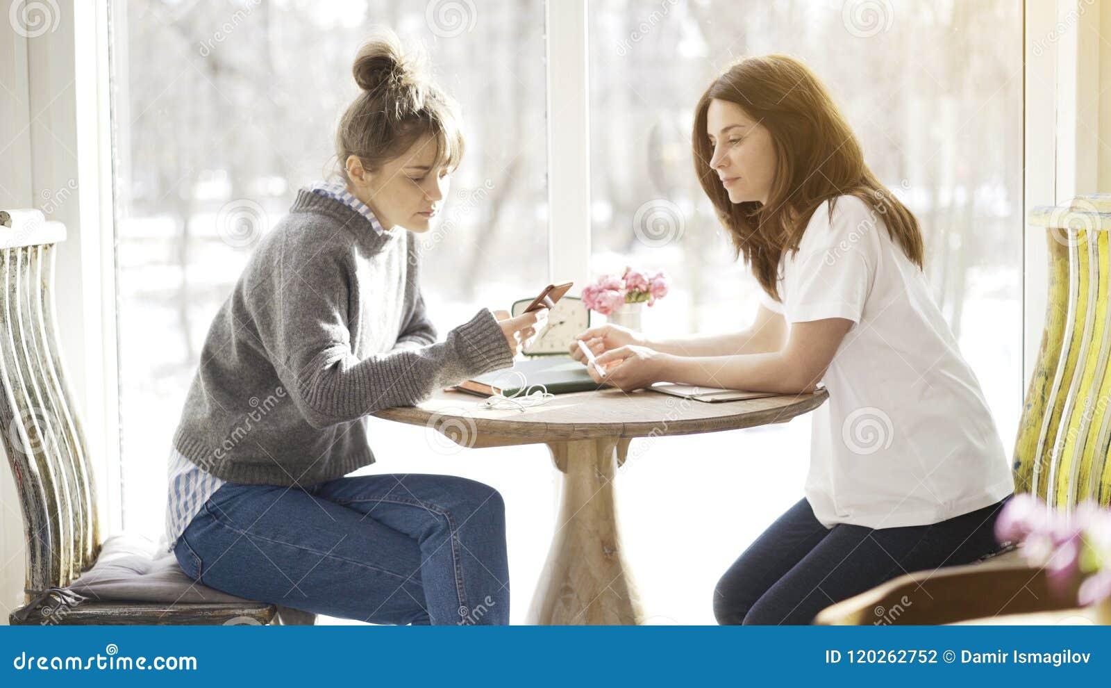 2 женских друз сидя в кафе лицом к лицу