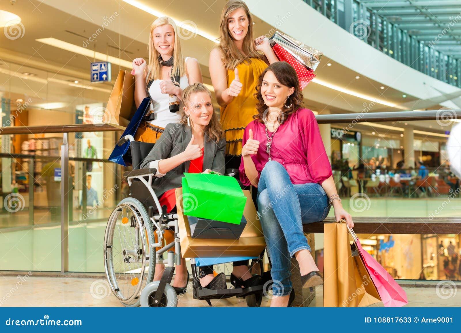 4 женских друз ходя по магазинам в моле с кресло-коляской