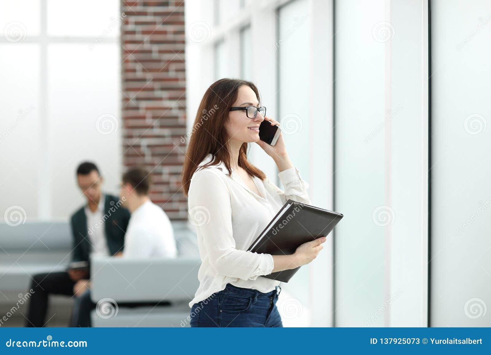 Женщина административного вопроса с доской сзажимом для бумаги говоря на мобильном телефоне