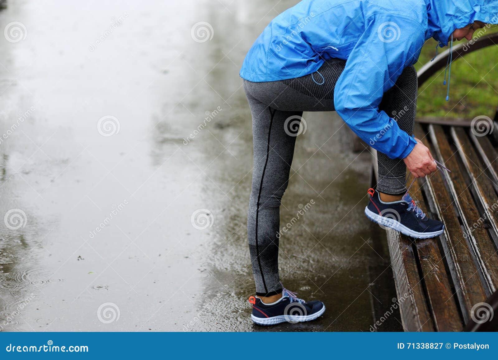 Женщина бегуна связывая шнурки перед тренировкой в дожде Марафон