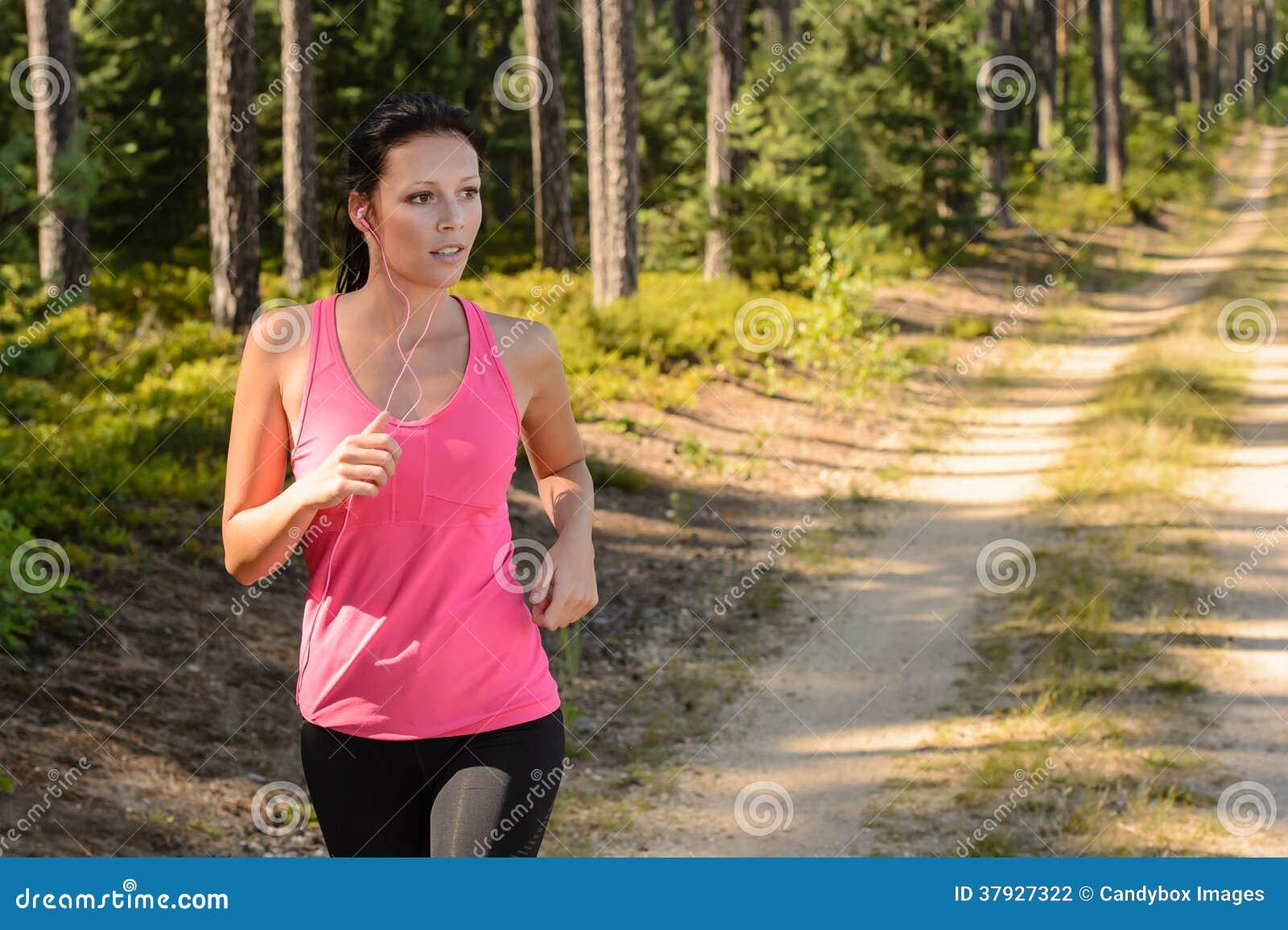 Женщина бежать через тренировку леса внешнюю