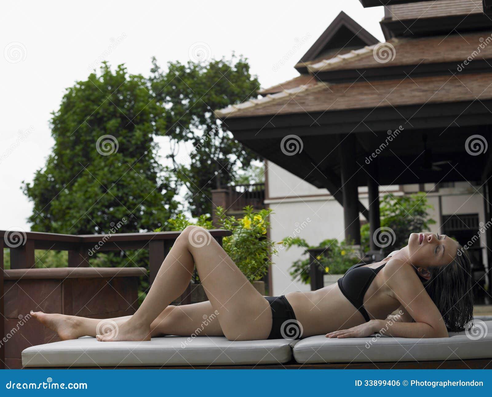 Женщина бикини отдыхая на Deckchair