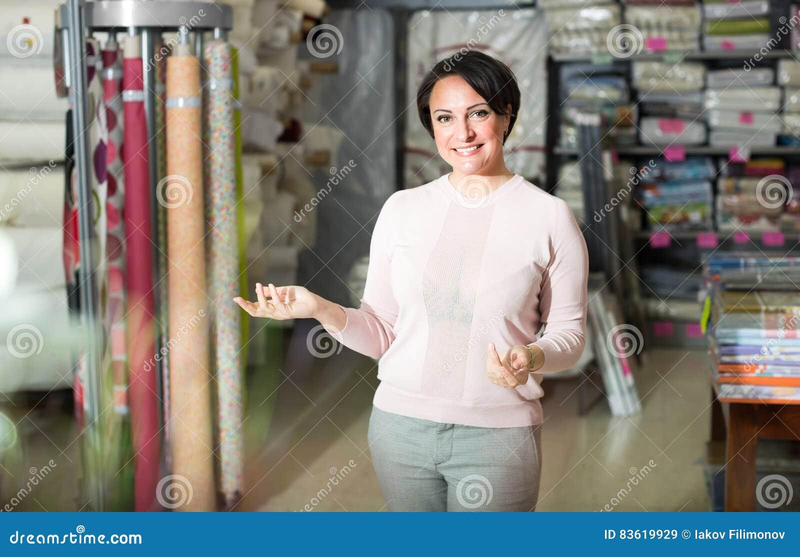 Женщина брюнет в магазине ткани