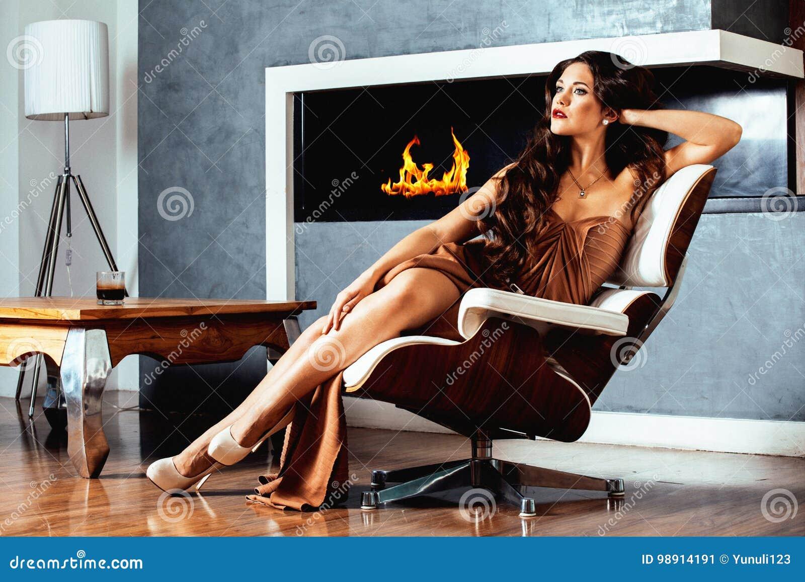 Женщина брюнет yong красоты сидя около камина дома