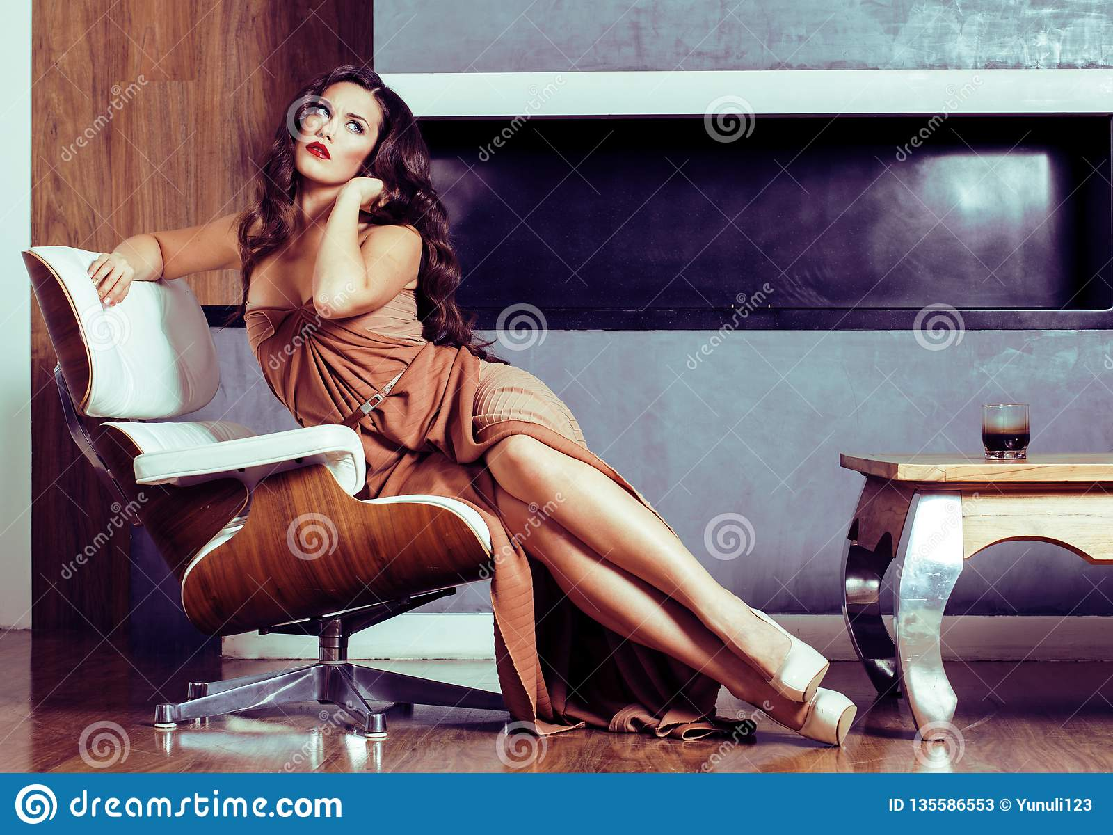 Женщина брюнет yong красоты сидя около камина дома, winte