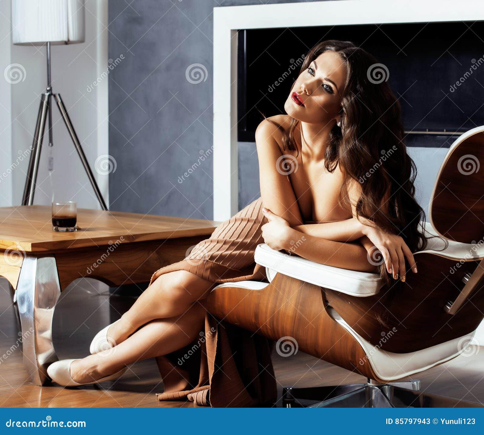 Женщина брюнет yong красоты сидя около камина дома, вечер зимы теплый в интерьере