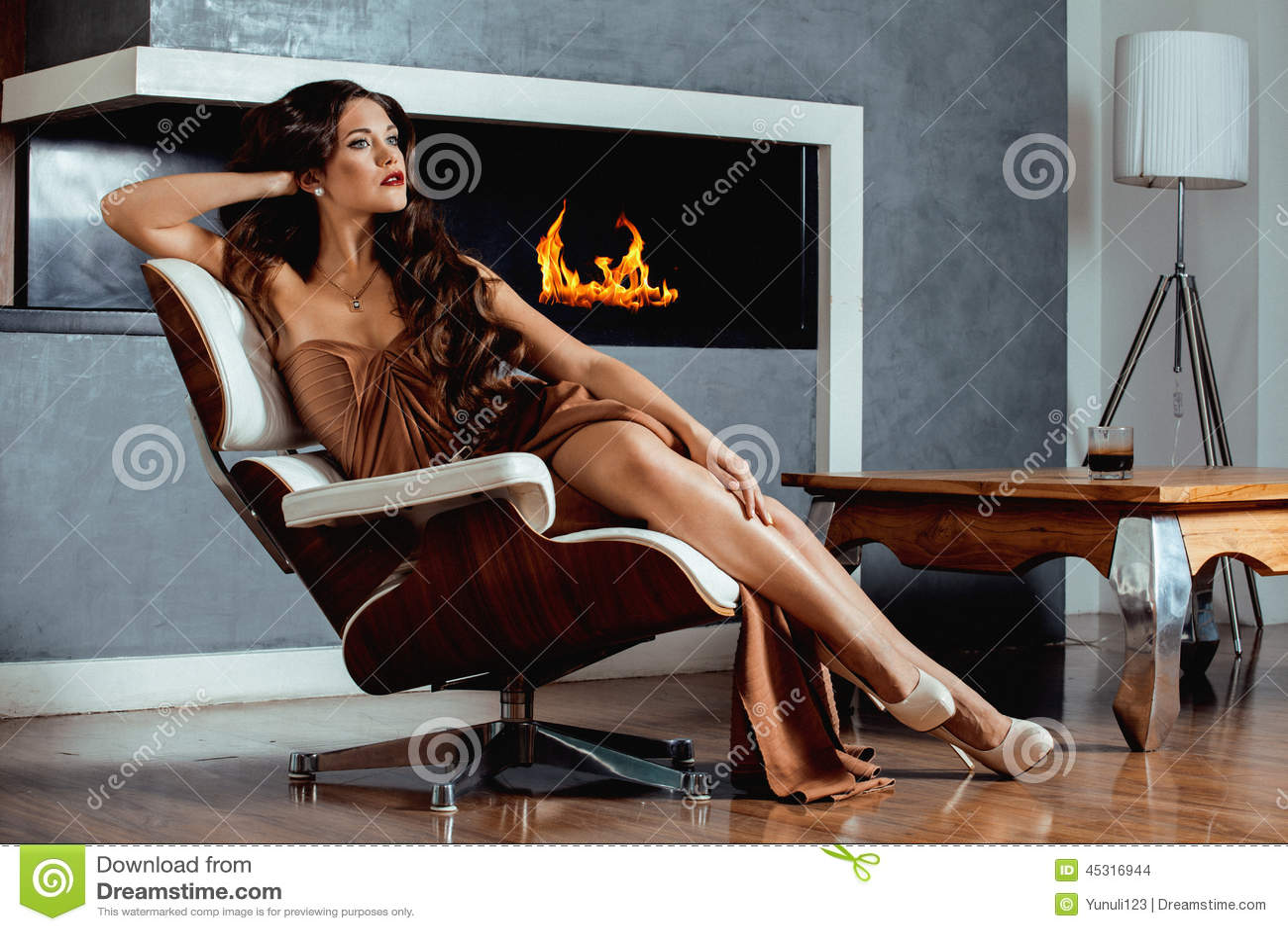 Женщина брюнет yong красоты сидя около камина