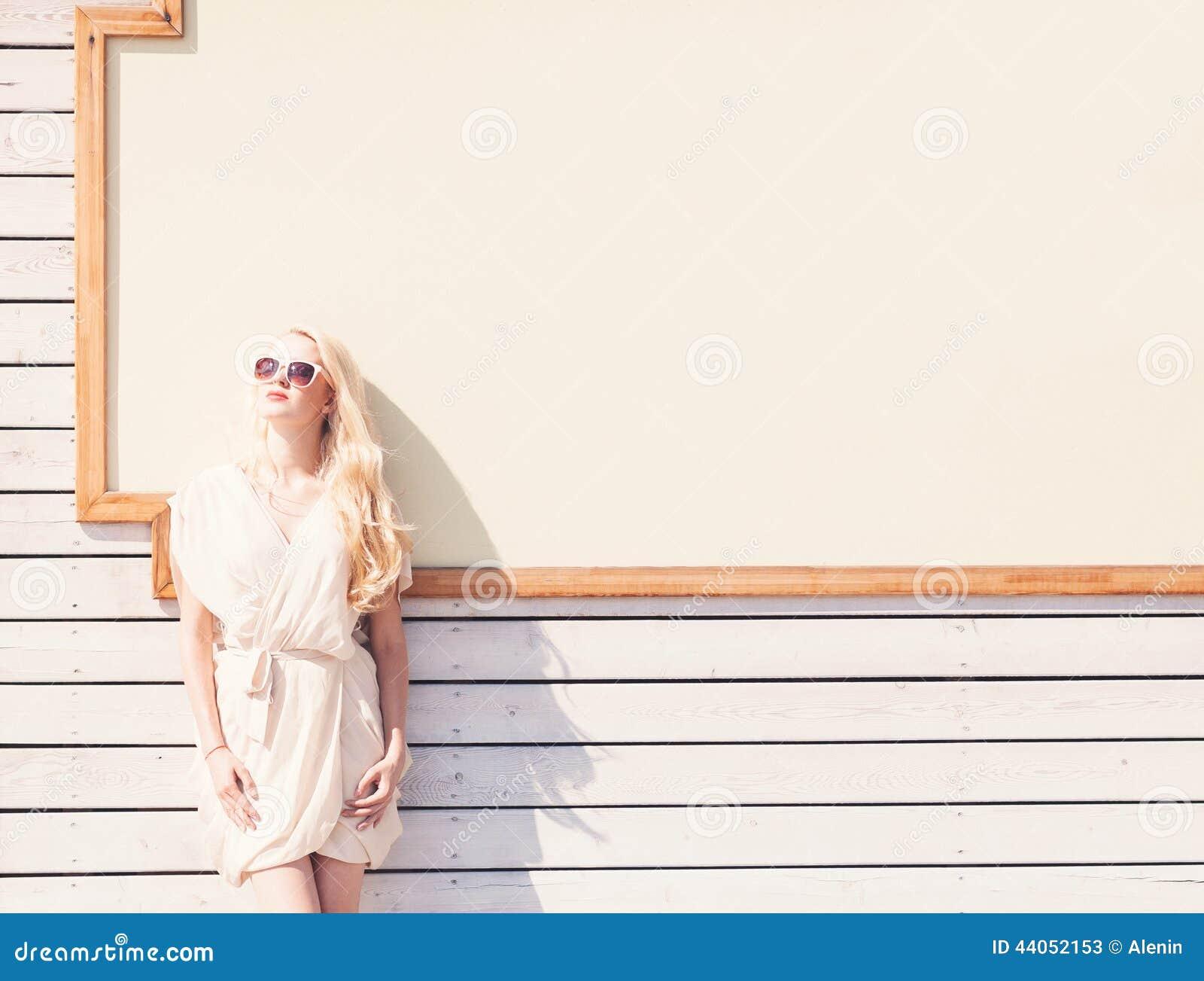 Женщина внешнего портрета моды лета чувственного красивая молодая белокурая белого платья в солнечных очках на улице на предпосыл