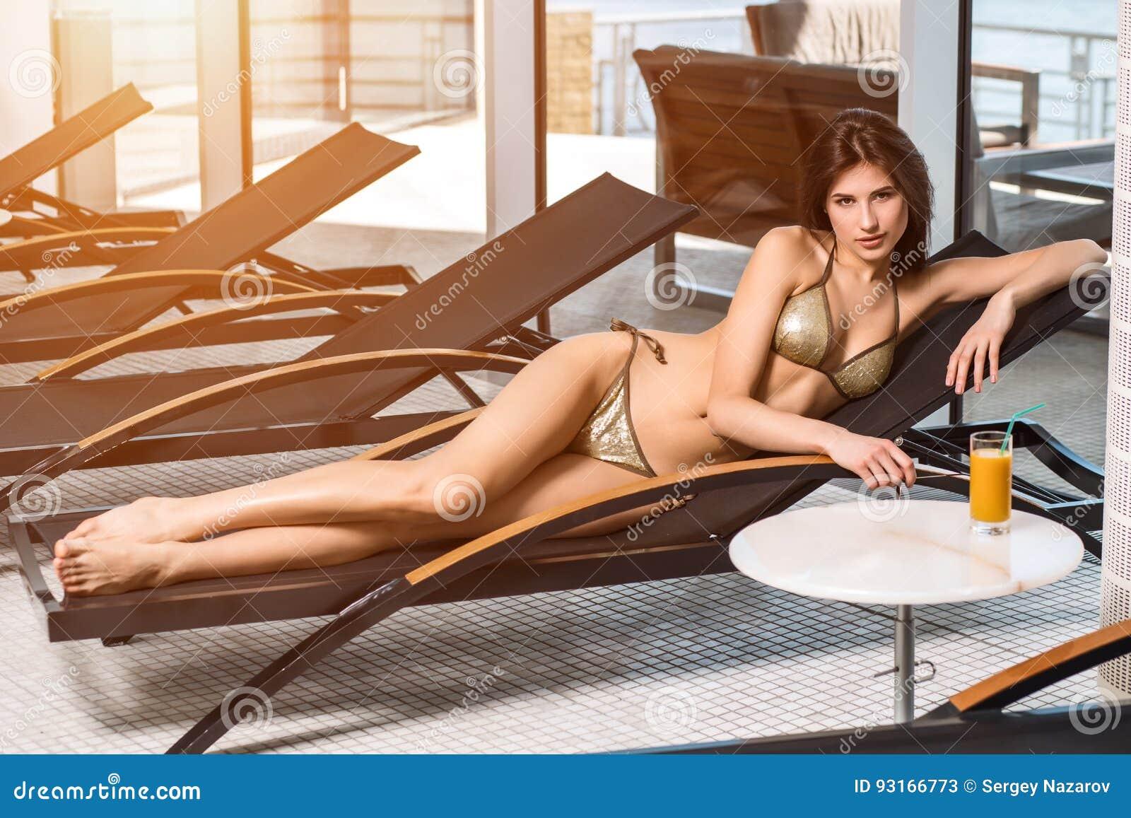 женщина воды спы здоровья ноги внимательности тела Женщина с совершенным телом в бикини лежа на deckchair бассейном
