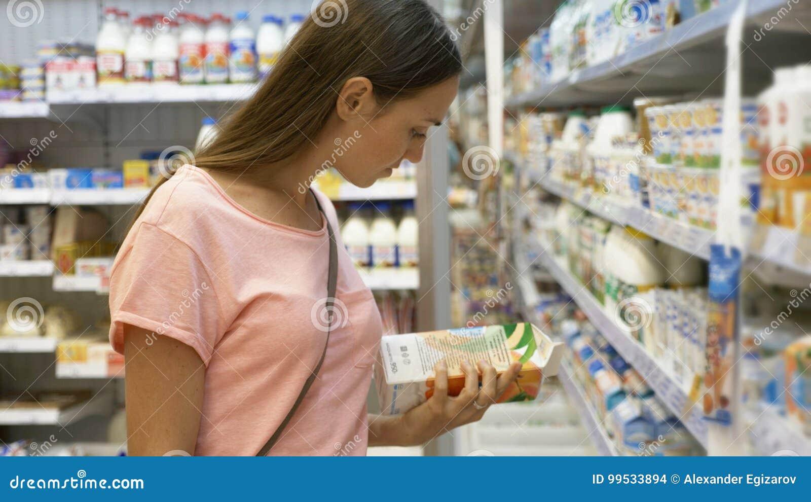 Женщина выбирая еду молокозавода в холодильнике на отделе бакалеи торгового центра