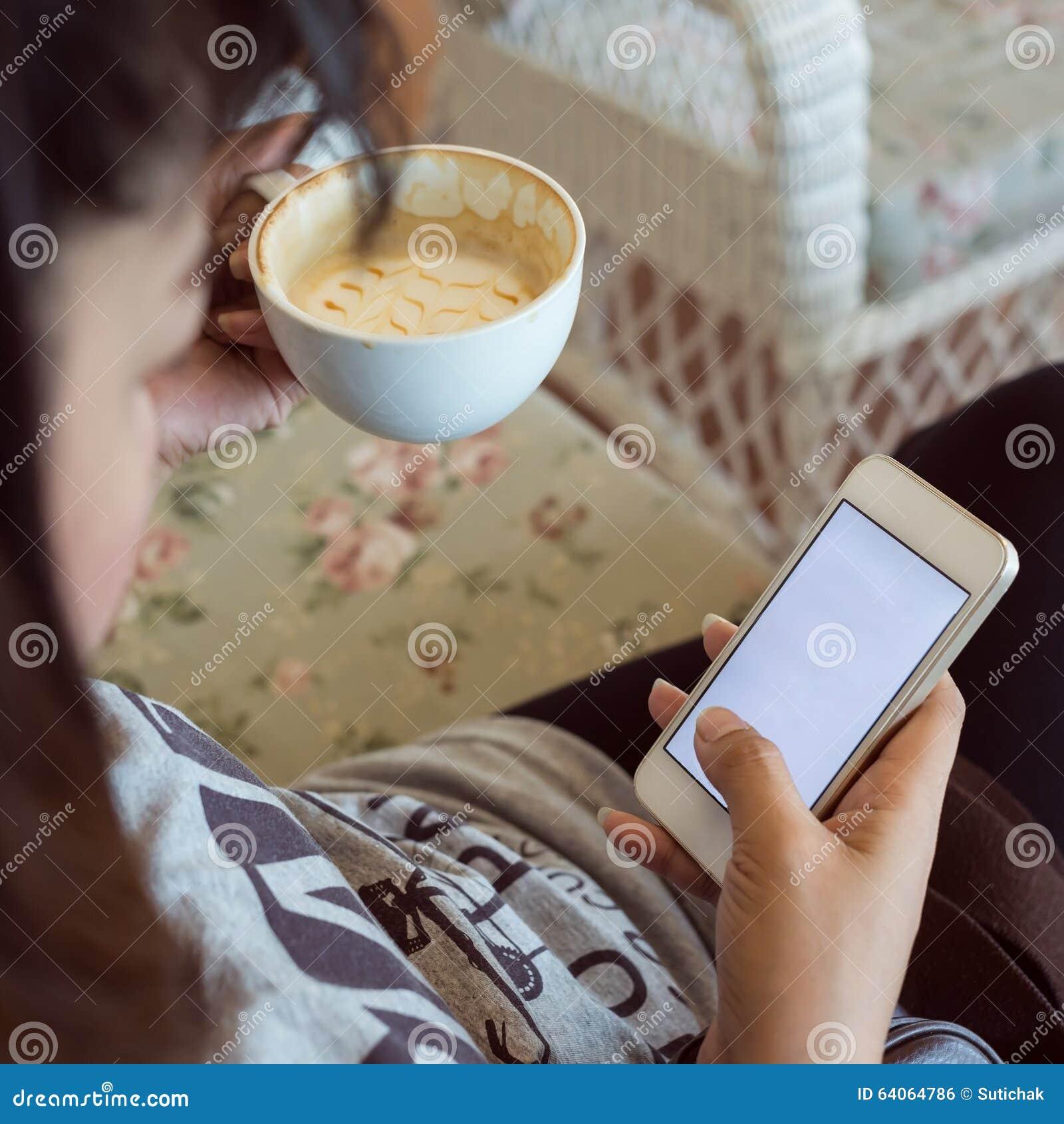 Женщина выпивая горячий кофе в кафе и использует мобильный телефон