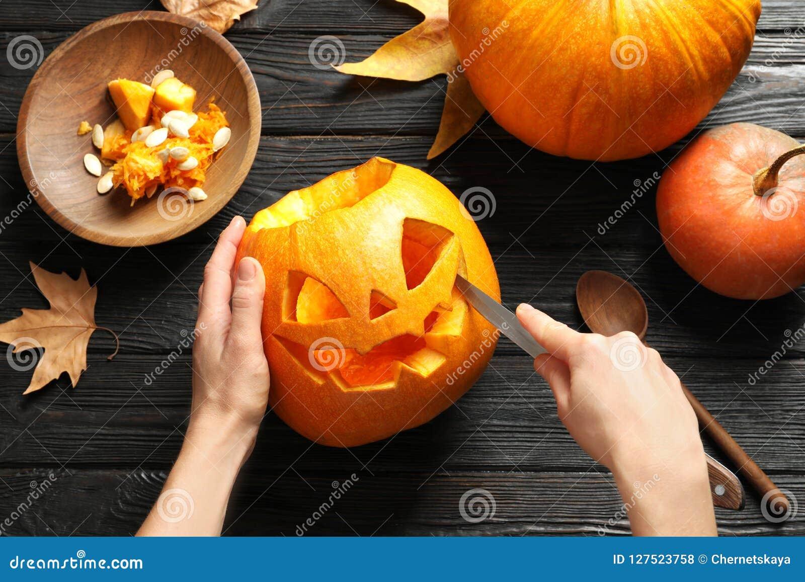 Женщина высекая фонарик jack головы тыквы хеллоуина на деревянном столе