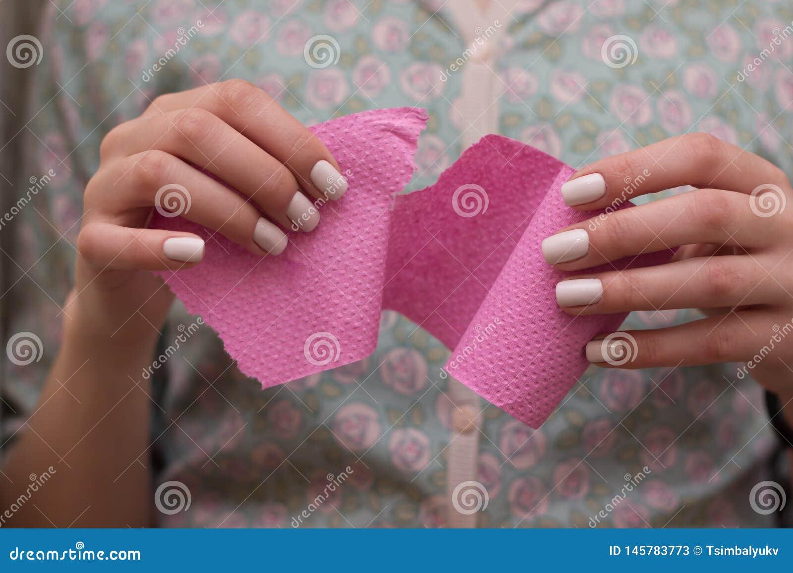 Женщина вытягивая ткань туалетной бумаги